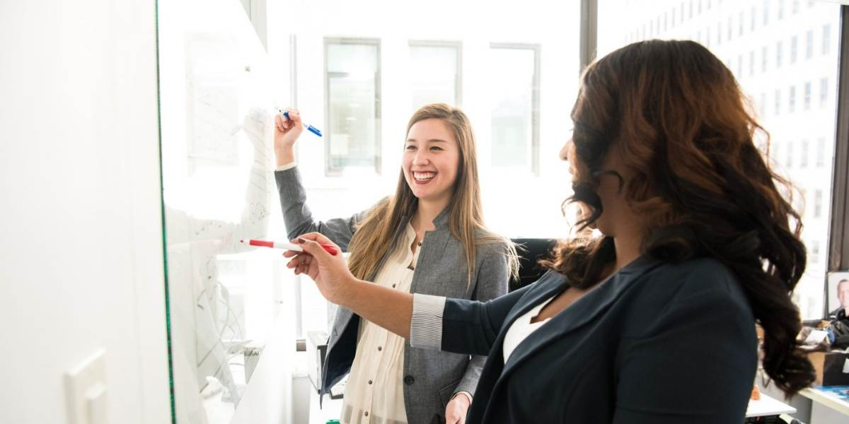 Two smiling women in a positive corporate culture