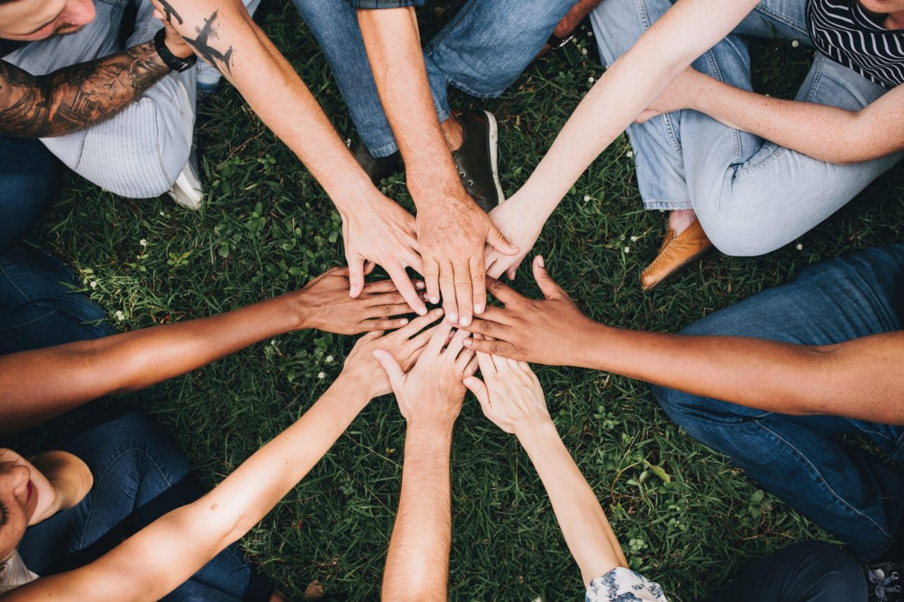 People huddled in a circle with hands in the middle