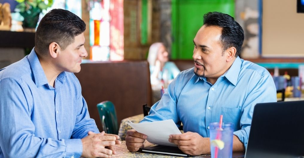 Two men in an interview at a restaurant