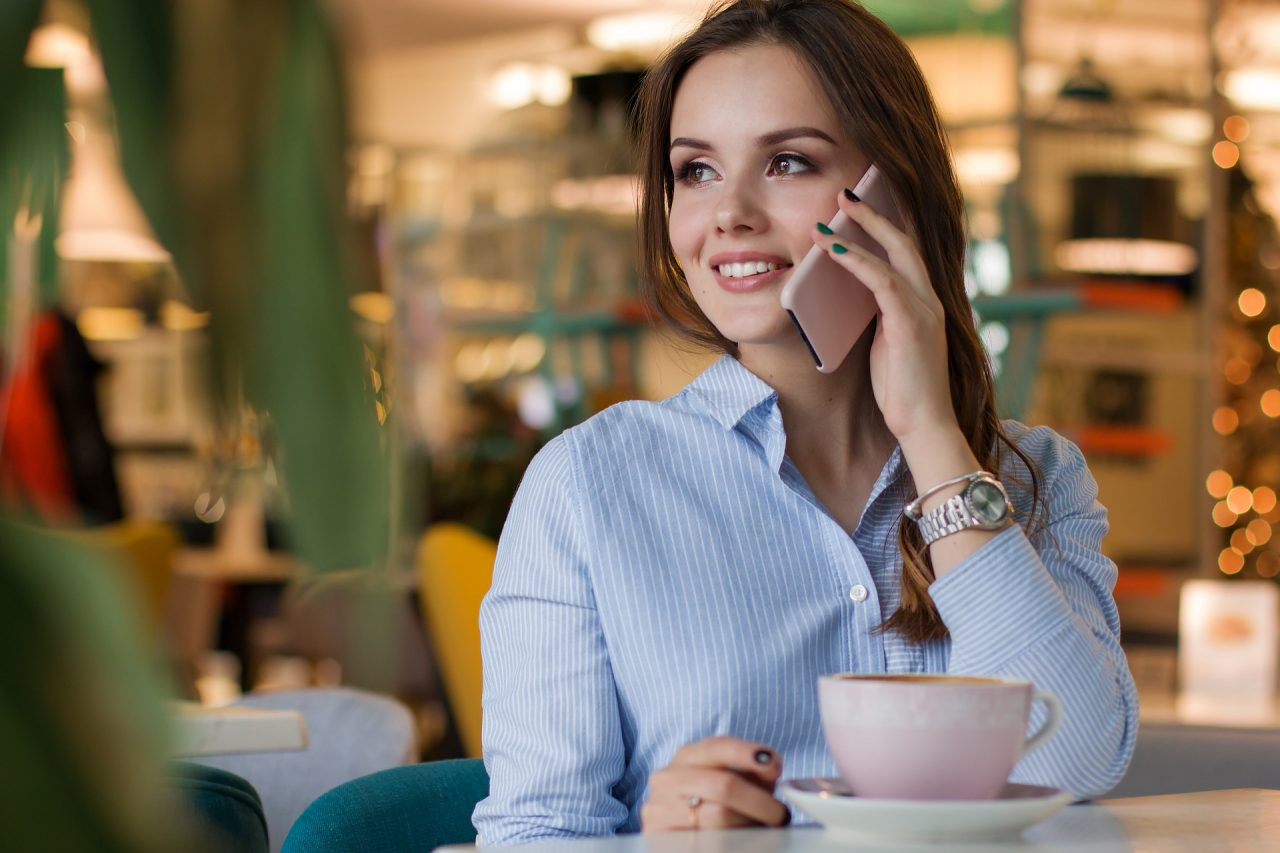 A woman on the phone and drinking coffee