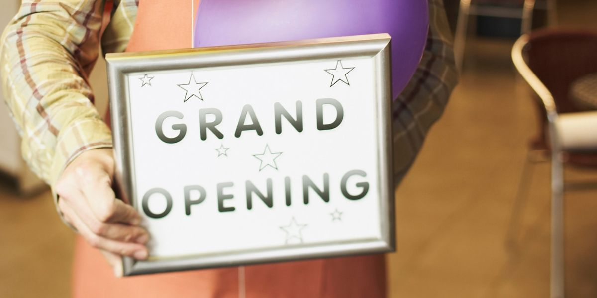 """Someone holding a sign that reads """"GRAND OPENING"""" for a franchise"""