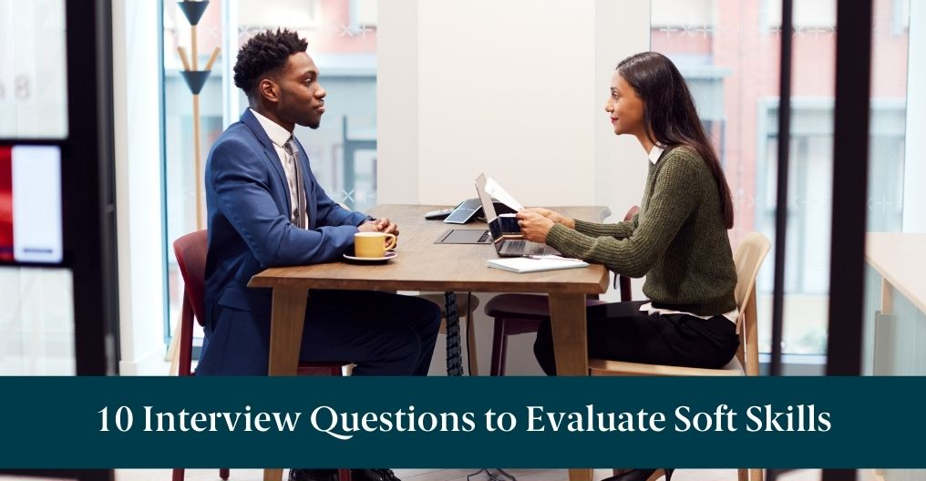 """Two people sitting at a table with text reading """"10 Interview Questions to Evaluate Soft Skills"""""""