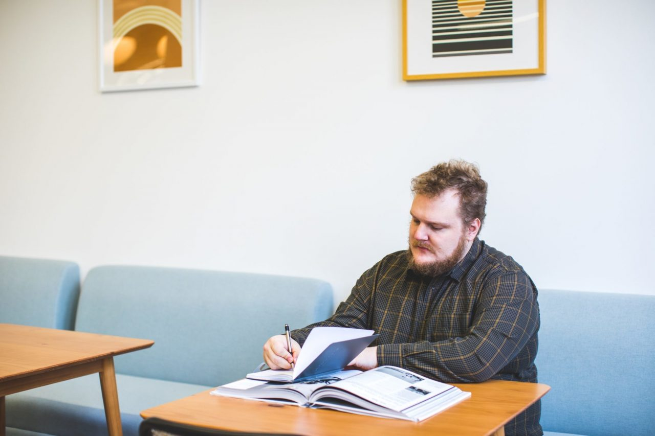 A man in the workplace, reading paperwork