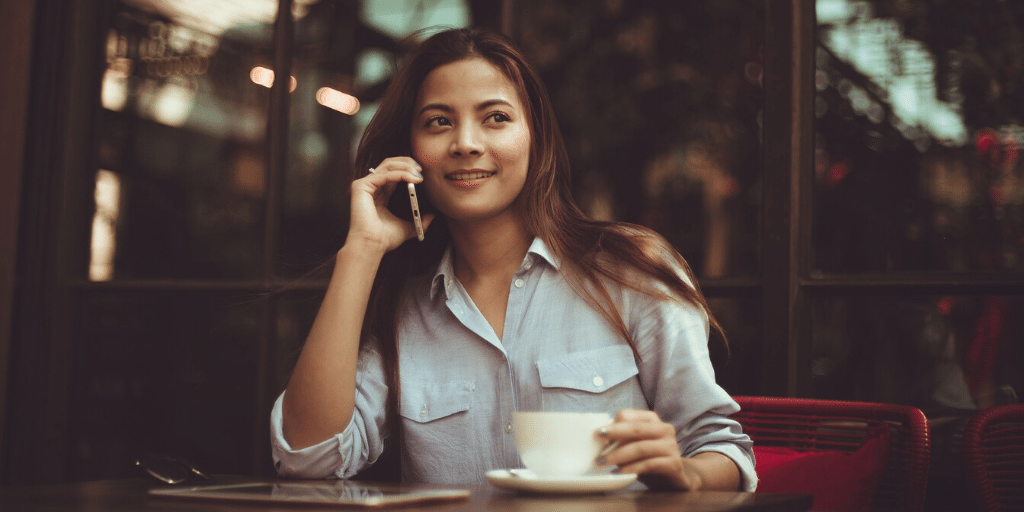 A woman on a phone interview at a cafe