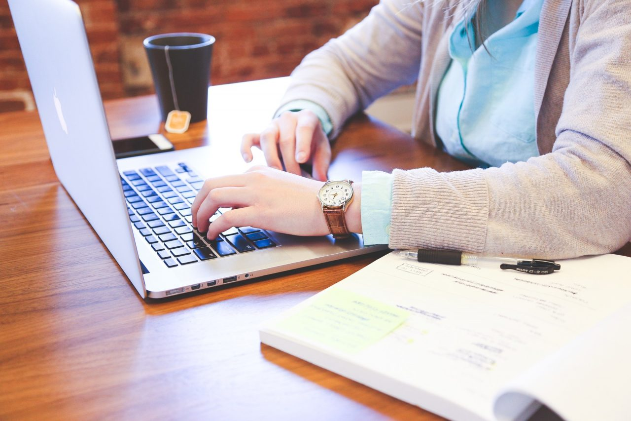A woman on a laptop researching workplace benefits to retain millennials