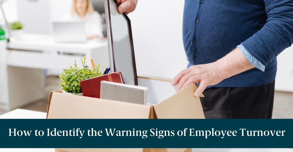 """Someone packing up their desk with text reading """"How to Identify the Warning Signs of Employee Turnover"""""""
