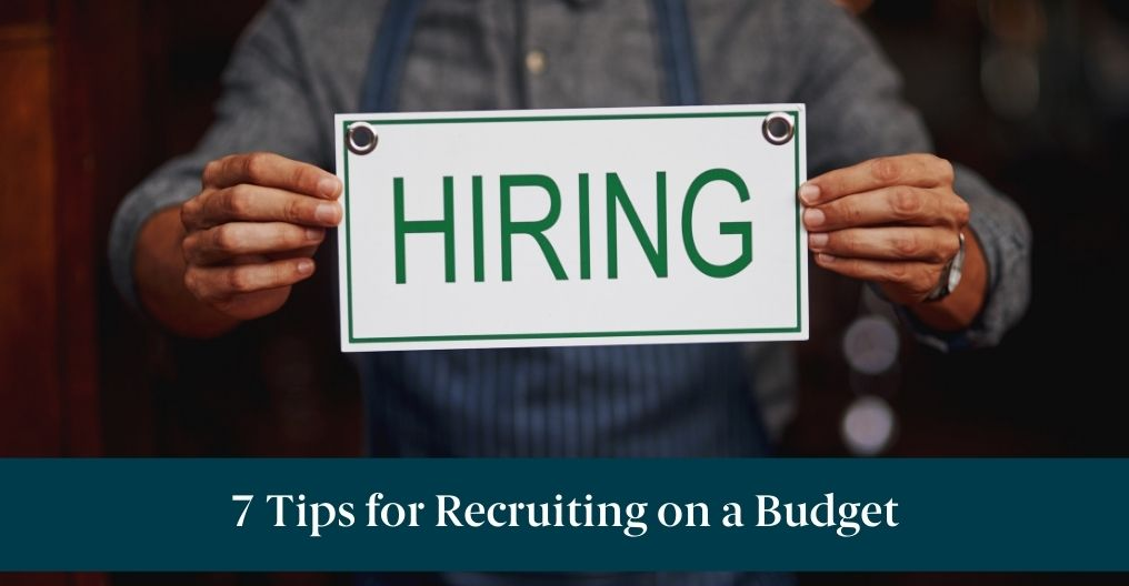 """Someone holding a """"Hiring"""" sign with text reading, """"7 Tips for Recruiting on a Budget"""""""